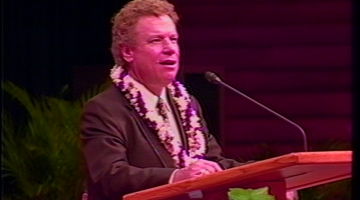 A photo of Buddy Youngreen giving a talk at the podium.