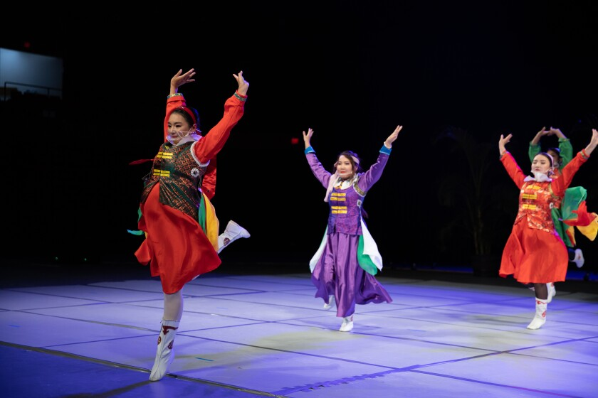 Women wearing purple, red and green dresses leap with their hands up on a white floor with a black background.