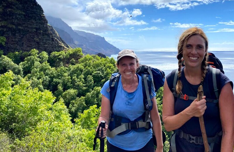 Rebekah Strain stands in the middle in a blue shirt and hiking backpack with another girl on her right wearing a dark blue shirt and hiking backback with green trees, mountains and the ocean behind them.