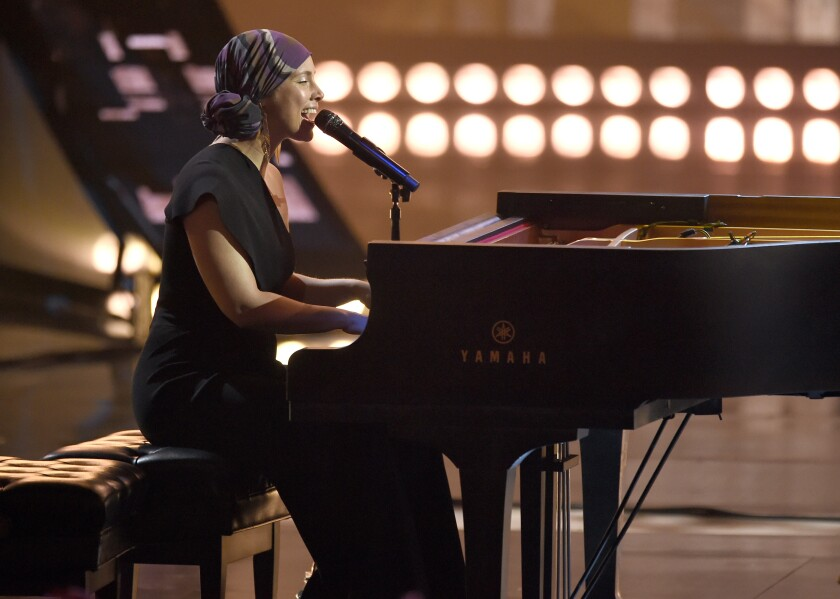 Alicia Keys performs on a piano during a concert.