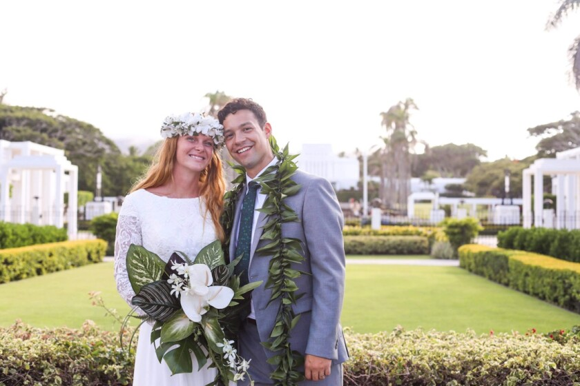 Anne Tobon wearing a white wedding dress, flower haku in her hair and holding a green and white bouquet stands next to her newly married husband, Sam Tobon, wearing a suit and ti leaf lei standing together in front of the Laie Hawaii Temple.