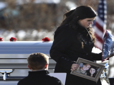 Kirk Takeshi Fuchigami's wife holds a picture of them while walking by the gravesite during the funeral