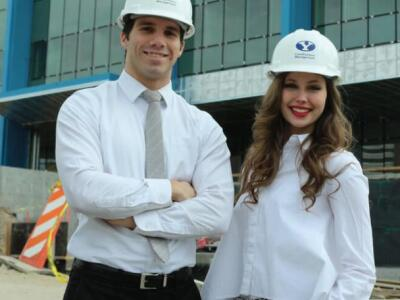 Two construction management students in front of a new building