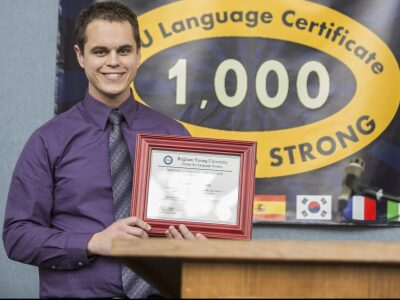 A BYU student holds a certificate during a ceremony to award the 1,000th language certificate