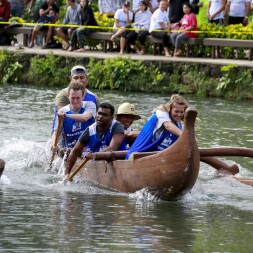 A group of 5 students wearing jerseys in a Polynesian style canoe paddling in a canoe race.