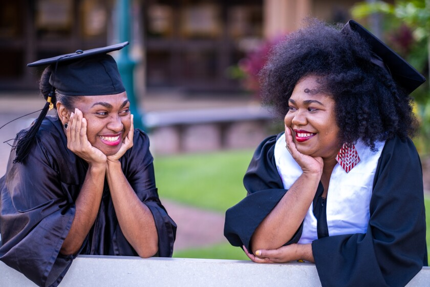 Photo of Adriannah and Fidelish Metta smiling looking at each other wearing their black graduation gowns and caps.