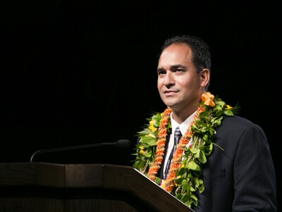 A tan-skinned man with short dark hair wearing a black suit and tie and green and orange leis standing behind a podium.