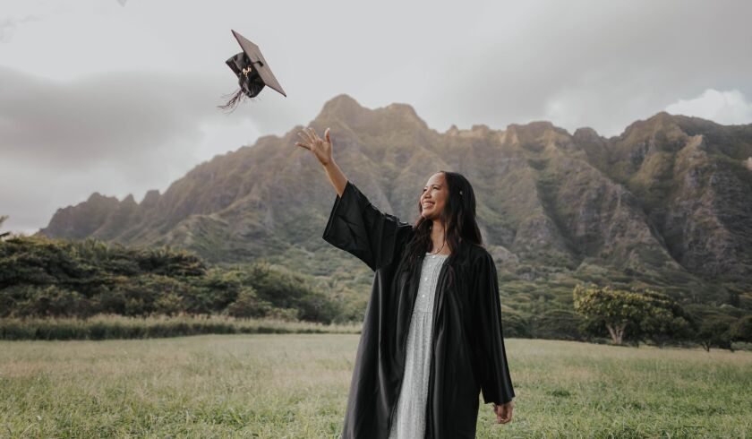 Mahe stands in graduation gown throwing her cap in the air while wearing a white dress with green mountains and fields in the background.