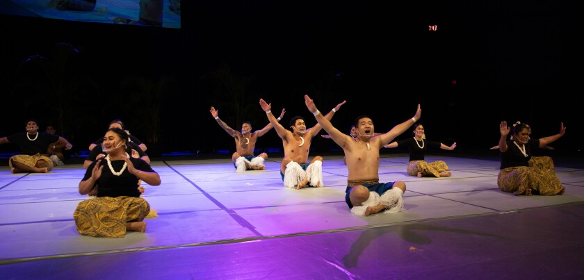 Men in a line wearing blue skirts and white cloth on their calves sit with their arms raised speaking with women on both sides of them wearing black shirts and yellow and black Polynesian-designed skirts on a stage with purple light on it.