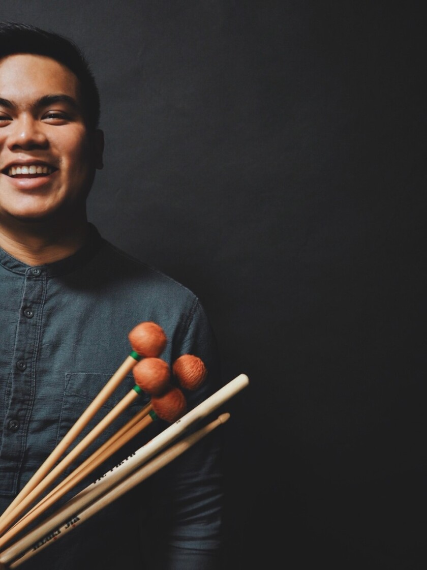 Kris Krisanalome poses for a photo with his drum sticks