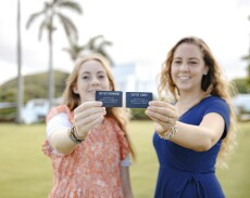 Two sister missionaries, one wearing an orange floral patterned dress and one in a blue dress, hold up their name tags in front of the Laie Hawaii Temple.