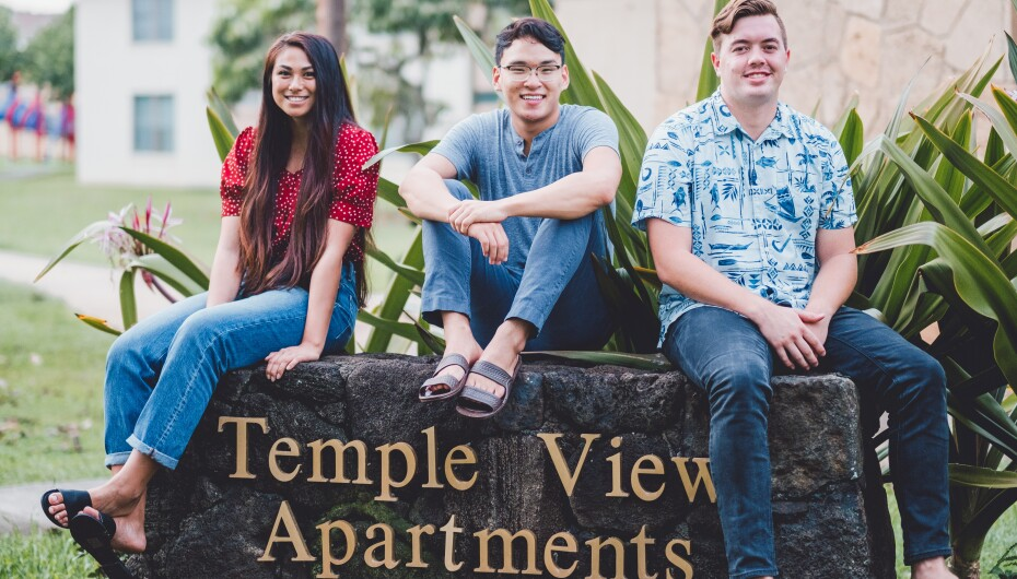 Faryn Taotafa, Yin Kim and Kawika Brubaker sit on the entrance sign to the Temple View Apartments in Laie