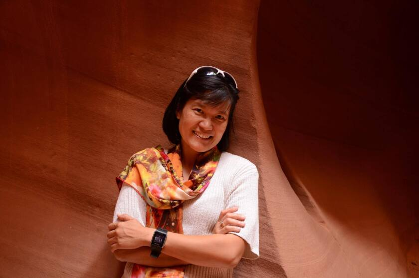 Joyce Tan wearing a white shirt and scarf smiling and folding arms leaning against the red-brown canyon wall.