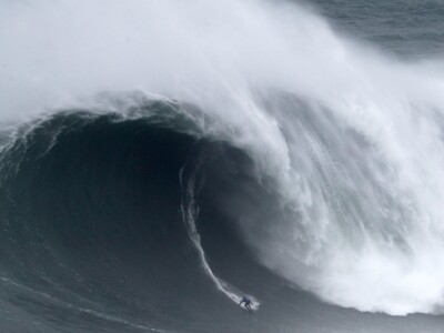 A surfer rides a wave that begins to crest above him