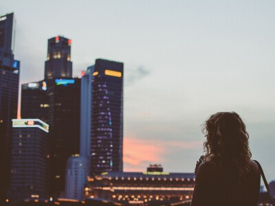 A professionally dressed woman looks out over a city skyline.