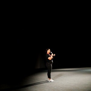 A woman speaking into a microphone on a dark stage.