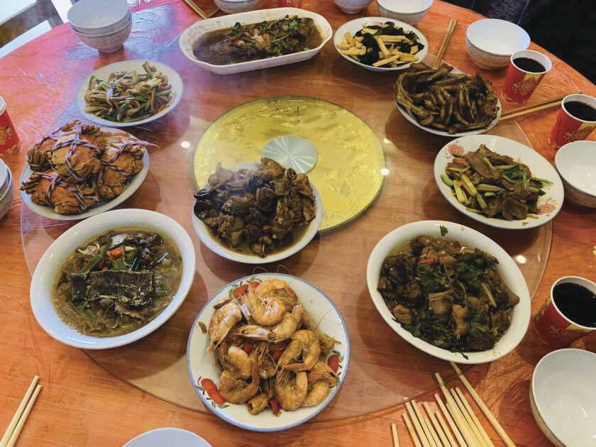 A large round table with a clear glass Lazy Susan holds 10 different Chinese dishes in white bowls and platters.
