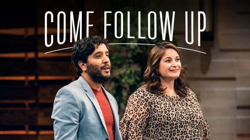 "Man wearing red shirt and light blue suit jacket and woman wearing leopard spotted shirt stand on set with white words behind them that say ""Come Follow Up."""