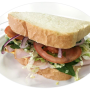 photo of a turkey sandwich with shredded lettuce, tomato, on white bread.