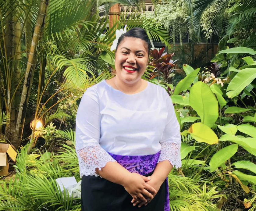 Sosefina Finau stands in front of foliage.