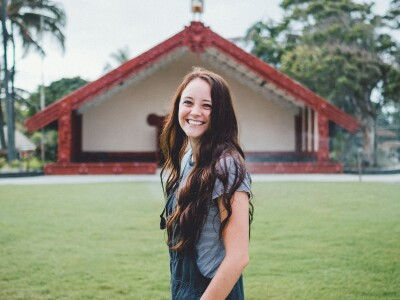 Madi Berry smiles with her hair down in front of the Aotearoa Village at the PCC.