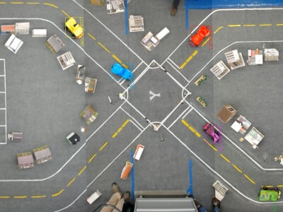 Aerial view of a miniature city with self-driving cars.