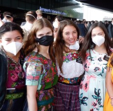 "Sister Payne and other sister missionaries wear masks as they stand behind the airport titled, ""Aeropuerto Internacional La Aurora."""