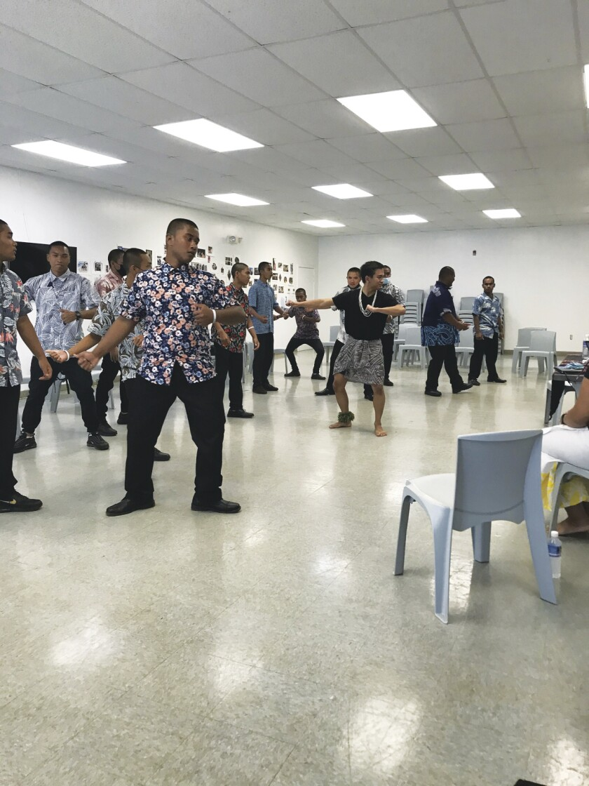 BYUH volunteers teaches young people at the Hawaii National Guard Youth Challenge Academy how to perform a Polynesian dance. They are dressing in dark pants and aloha shirts.