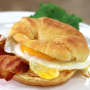 This is a photo of a breakfast sandwich. The sandwich consists of sliced, toasted croissants with eggs, bacon, and cheese inside.
