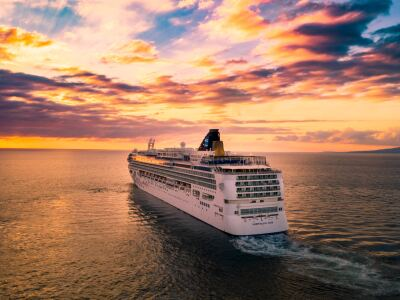Image of a cruise ship sailing into the sunset