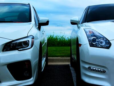 Two white sedans side by side with grass in the background