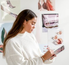 Gabrielle Pritt stands wearing a white sweater while drawing on her ipad with a white wall and posters in the background.