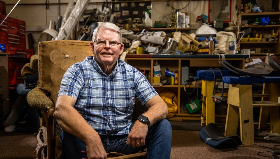 Professional portrait of BYU employee Wayne Martin sitting in his upholstery shop.