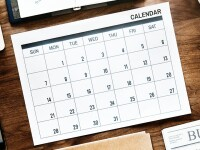 A calendar placed among other objects on a desk.