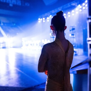 A dancer watches a performance from just off stage.
