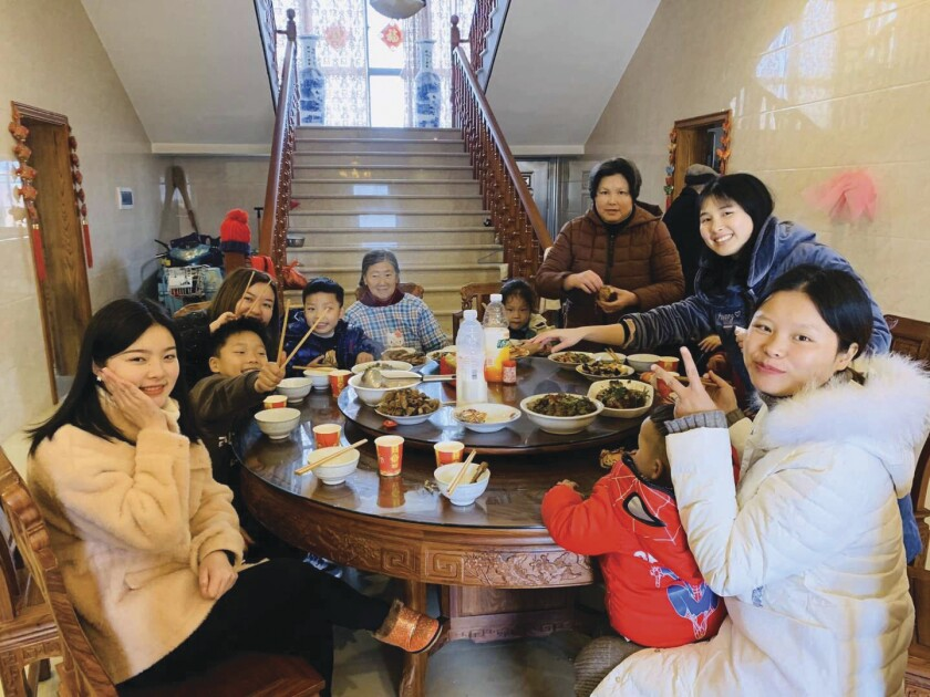 Fei Liu and her family of six women and four children sit around a large, round table eating a meal in white bowls of rice and a variety of main dishes.