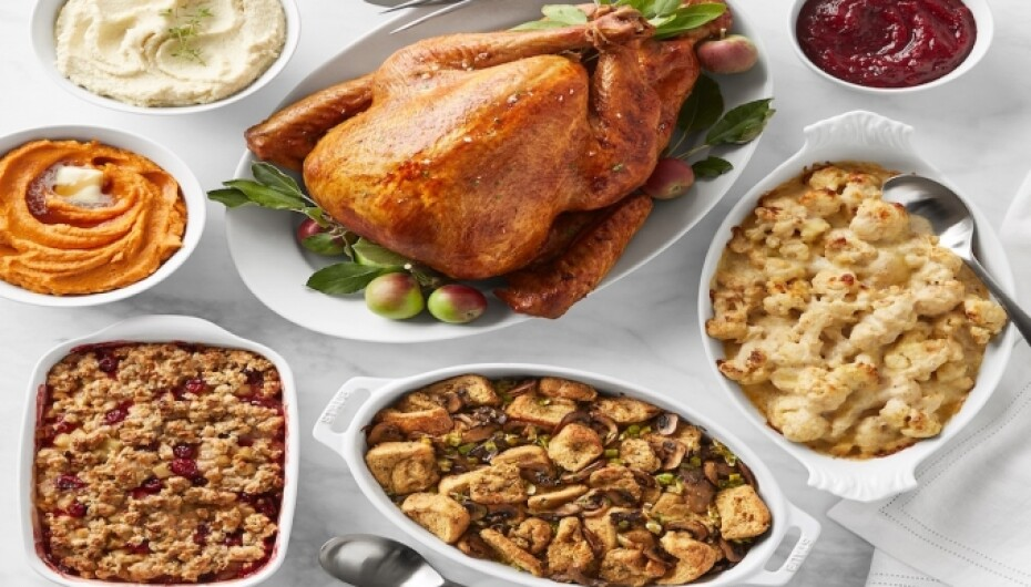 Various Thanksgiving dishes spread around a white table