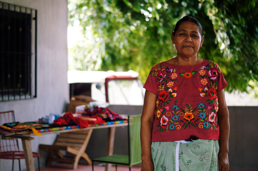 Photo of Mexican woman stands in an embroidered shirt with a house in the background.