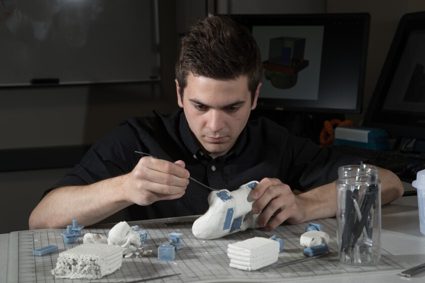 Student Andy Bryce works molds a game controller out of clay