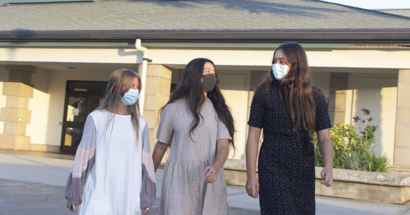 Photo of three women wearing masks and church dresses walking outside the stake building