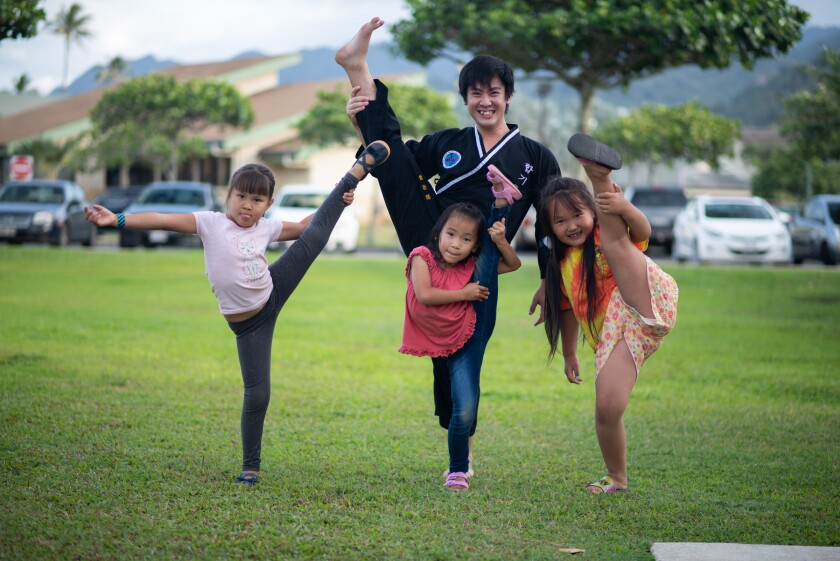The Hopkido instructor wearing his black top and pants lifts one leg straight up in the air along with three of the young girls he teaches out of the grass outside of the apartments they live in a campus.