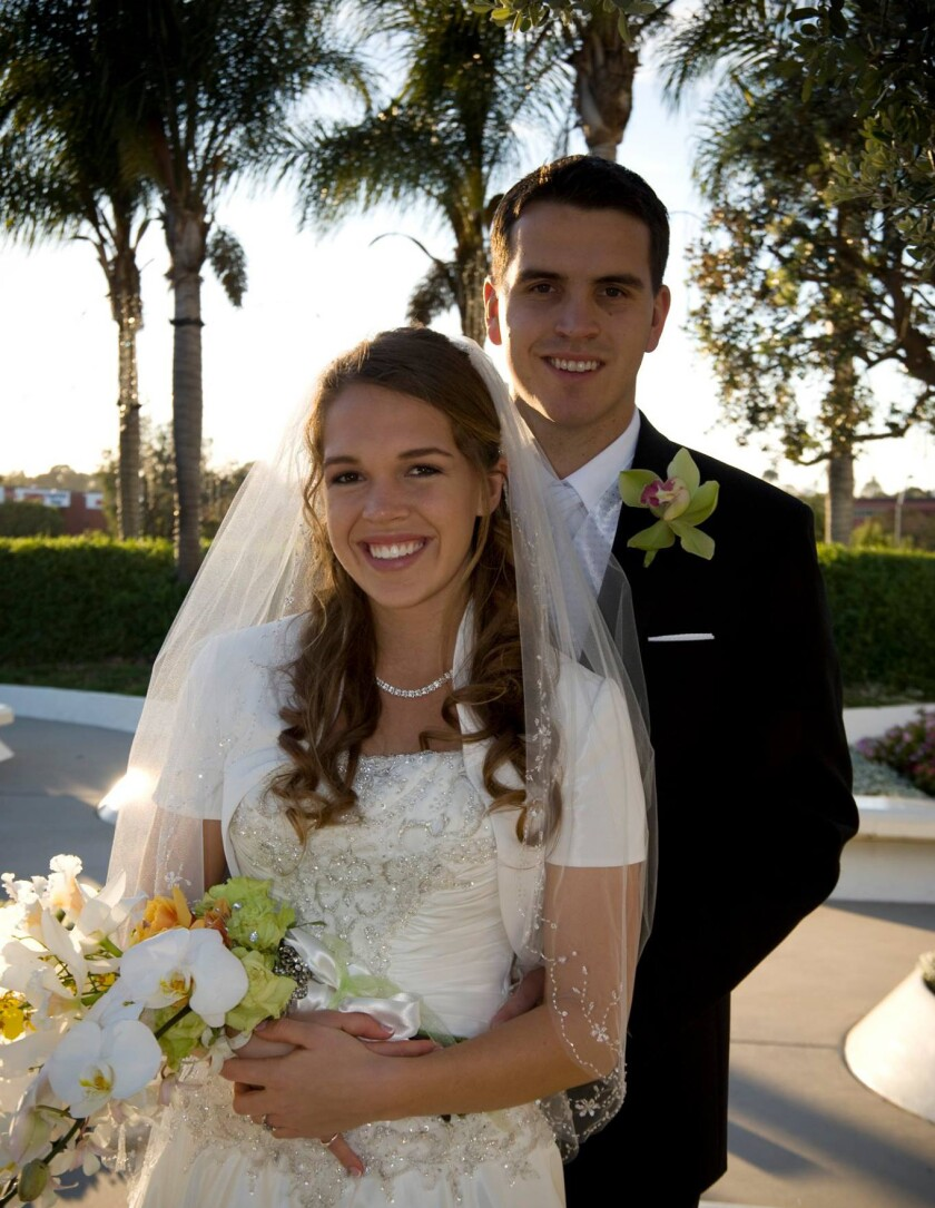 Shenley Puterbaugh wearing a white wedding dress, veil and flowers in her hands with her husband behind her wearing a black suit and tie with palm trees behind them.