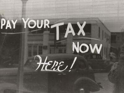 """An old window paiting that reads """"Pay your tax now here!"""""""