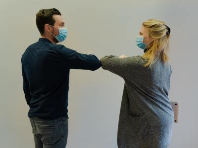 Man in black sweater and woman in grey sweater wearing surgical masks and touching elbows