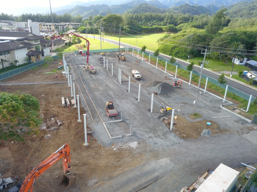 Aerial view of the construction area of the parking lot next to the HGB. Mikionele Way is on the right and HGB is on the left side of the parking. Steel Columns are up for the solar panels. Heavy machines are preparing the ground for pavement.