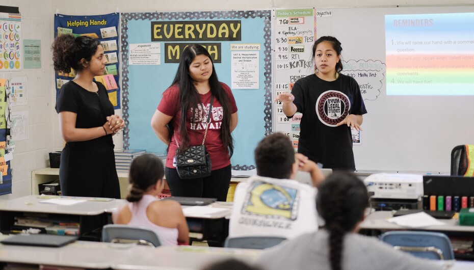 Three students from BYUH stand in front of a classroom full of fifth-graders.