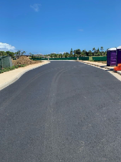 A close view of Mikionele Way Extension from Naniloa Loop side. The asphalt pavement looks complete. Temple View Apartments can be seen in the back of the photo.