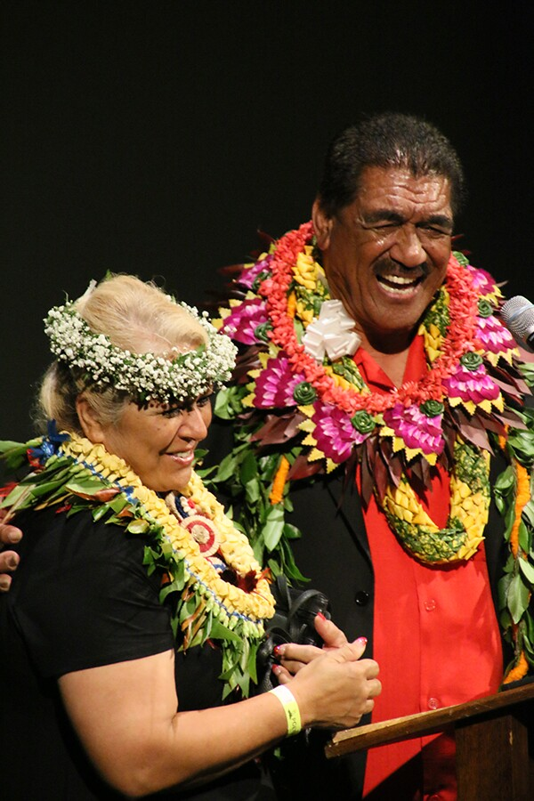 Junior and Almira Ah You stand at podium with leis and haku in Almiras hair with a black background.