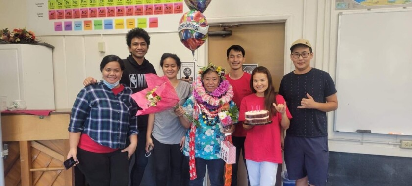 Mele Lavulavu with flower and other leis around her neck holding balloons, a gift bag and flowers with students smiling standing around her.