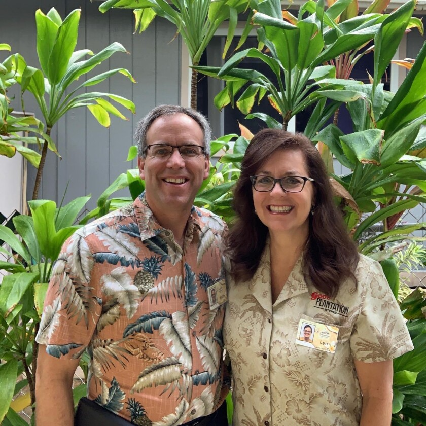 Sister and Elder Johnson smile wearing aloha shirts with PCC name tags with ti plants behind them.